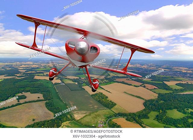 A red stunt biplane in flight over rural countryside