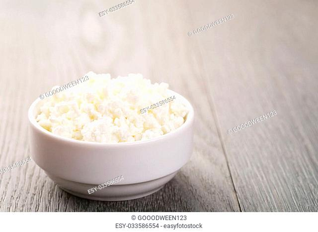 fresh cottage cheese in a white bowl on a wooden table, toned photo