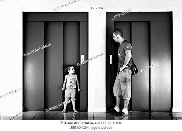 Little girl and man in front of elevator