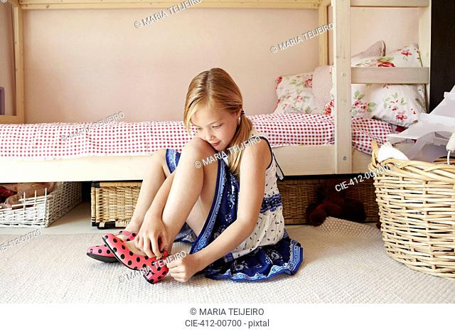 Girl in dress putting on polka-dot shoes in bedroom