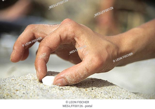 Italy, Sardinia, Man's Hand collecting shell, close-up