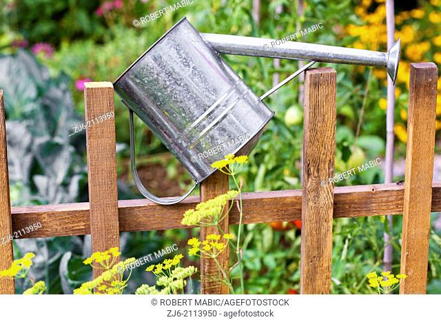 Watering can on a wooden fence