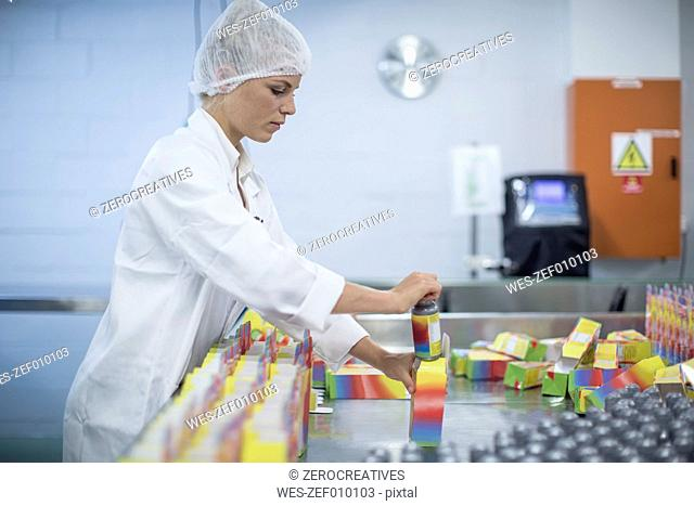Woman packing flasks in medical factory