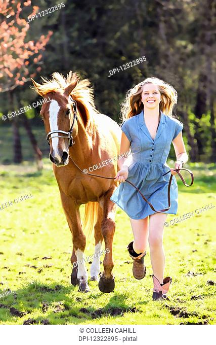 A young woman runs in a field with a horse; Oregon, United States of America