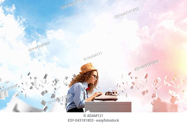 Young and beautiful woman writer in hat and eyeglasses using typing machine while sitting at the table among flying papers with cloudy skyscape on background