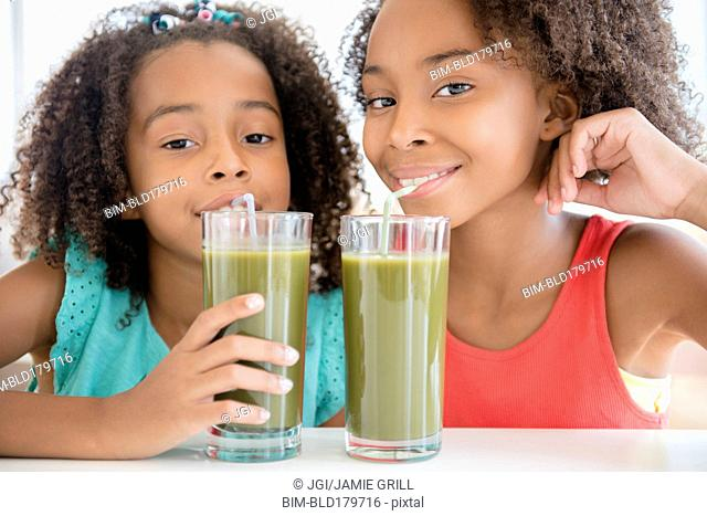 Mixed race sisters drinking healthy juice