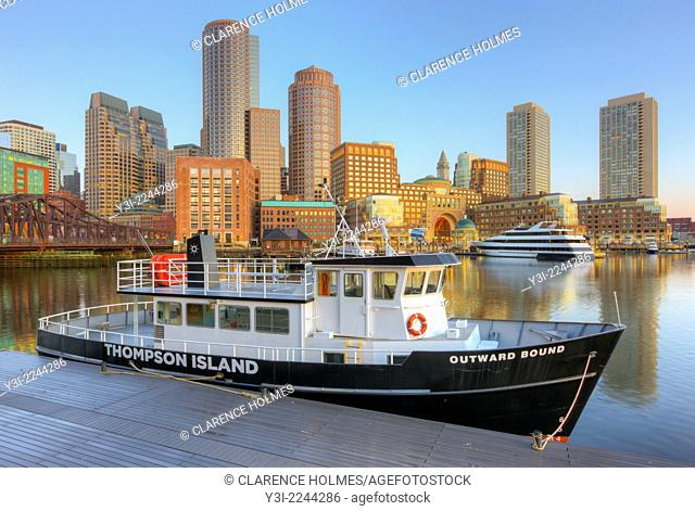 The Outward Bound Thompson Island Ferry sits moored in front of the skyline at sunrise in Boston, Massachusetts