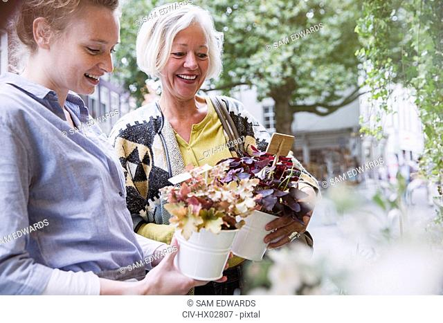 Florist showing potted plants to female shopper at storefront