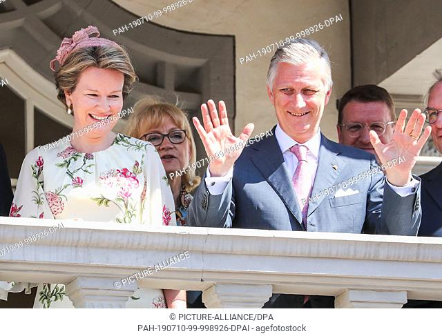 10 July 2019, Saxony-Anhalt, Wittenberg: The Belgian royal couple King Philippe and Queen Mathilde (M) wave from the town hall balcony in Lutherstadt-Wittenberg