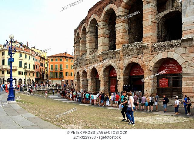 Visitors in front of the main entrance to the Roman amphitheatre Arena di Verona at the Piazza Bra square in the historic centre of Verona - Italy
