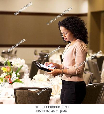 African American waitress using tablet computer in dining room