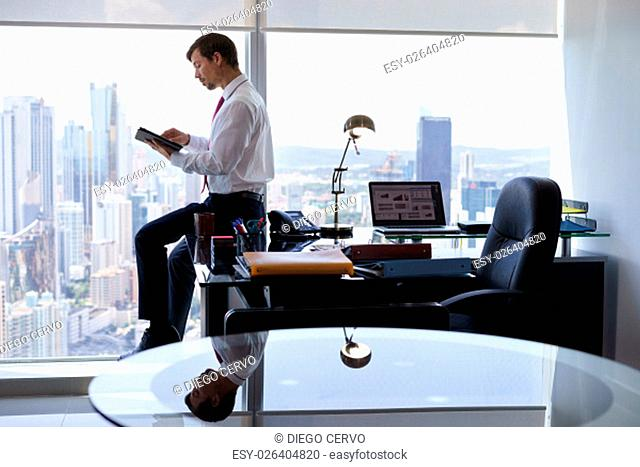 Adult businessman sitting on desk in modern office and reading news on tablet pc. The man works in a skyscraper with a view of the city from the large window