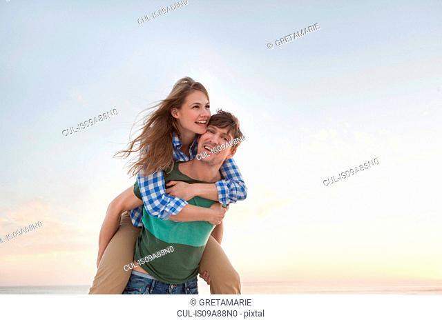 Couple on beach, man giving woman piggy back