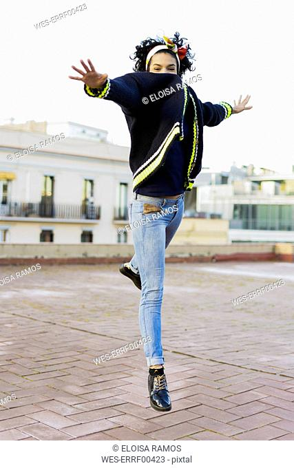 Portrait of happy young woman jumping in the city