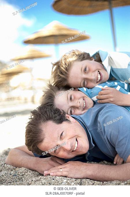 Dad with two sons in a pile on beach