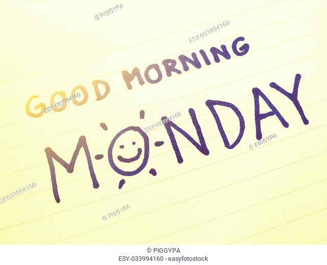 Hand writing on notebook with good morning Monday and hand draw smile, colored filter effect
