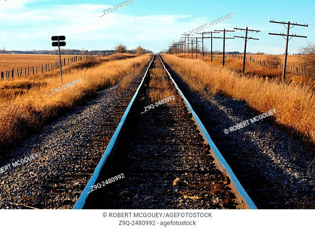 A landscape image of a set of railway tracks streaching straight traveling to the horizon in rural Alberta Canada