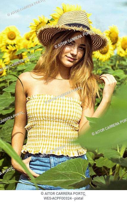 Young woman with a straw hat in a field of sunflowers
