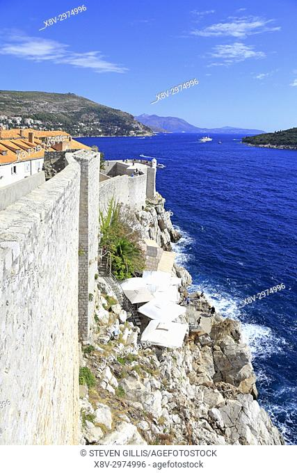 Restaurants on the rocks below Dubrovnik Old City walls, Croatia, UNESCO world heritage site, Dalmatia, Dalmatian Coast, Europe