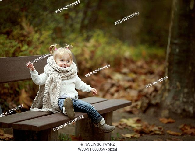 Blond little girl wearing big scarf sitting on a bench in autumn forest