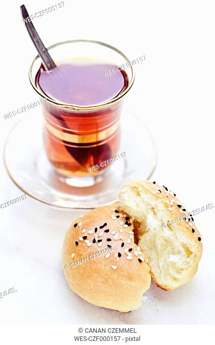 Glass of black tea and homemade Turkish yeast bread filled with sheep cheese