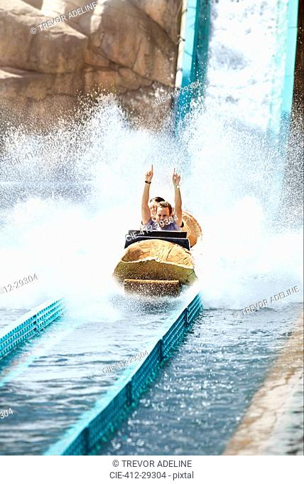 Enthusiastic young man riding water log amusement park ride