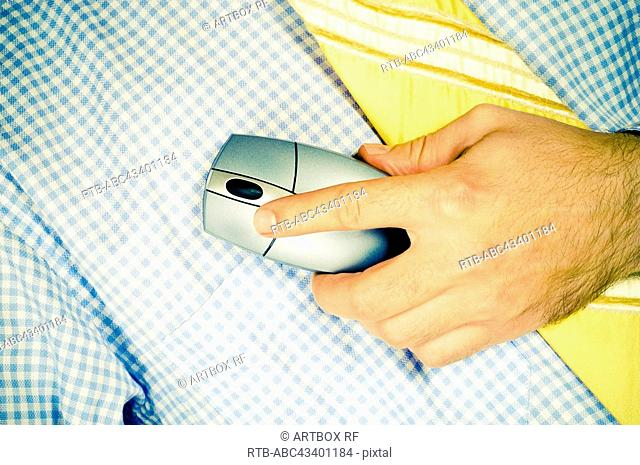 Mid section view of a man holding a computer mouse