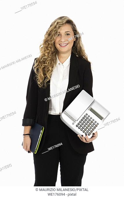 Businesswoman standing in the studio with computer and cash register under her arms, she is wearing a black suit and white shirt