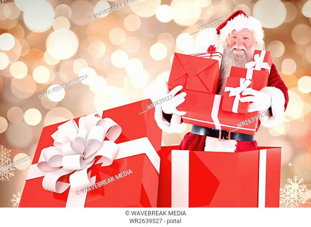 Portrait of santa claus holding christmas gifts
