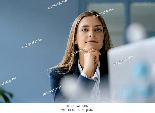 Portrait of a young businesswoman, working in office, using laptop