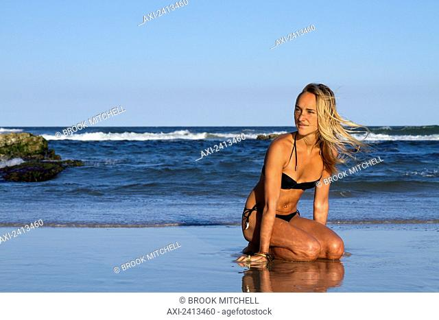 Young woman in a bikini at Seven Mile Beach, Byron Bay; New South Wales, Australia