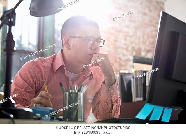 Hispanic businessman working at computer at office desk