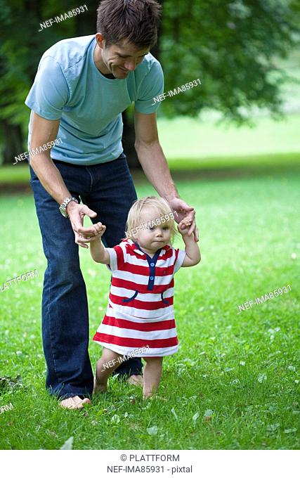 Mid adult father helping daughter with first steps