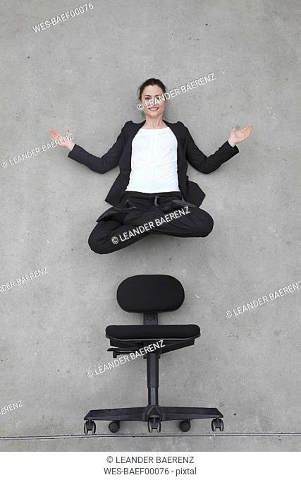 Businesswoman floating above chair, elevated view