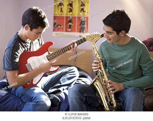 Two teenage boys playing musical instruments