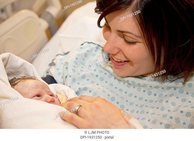 mother holding newborn baby daughter, edmonton, alberta, canada