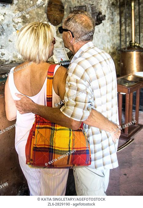 Older, mature, retired couple enjoying being together and watching a movie in the museum of a distiilery in Martinique