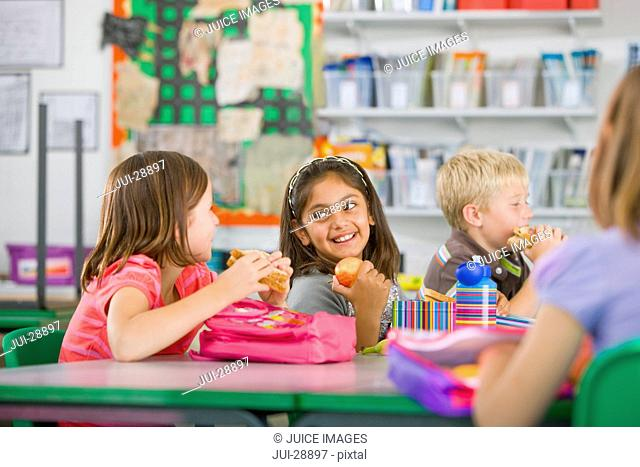 Smiling children eating lunch in classroom