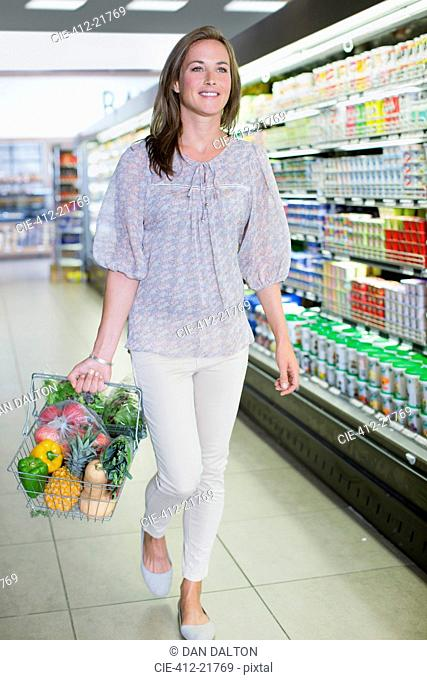 Woman carrying full shopping basket in grocery store