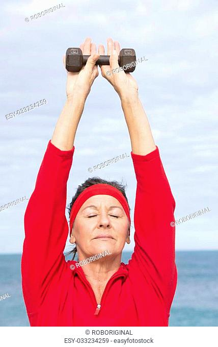 Portrait beautiful mature woman showing active retirement, excercising with weights arms up outdoor, positive, confident, energetic, closed eyes