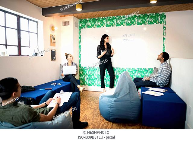 Young businesswoman giving whiteboard presentation in creative meeting room