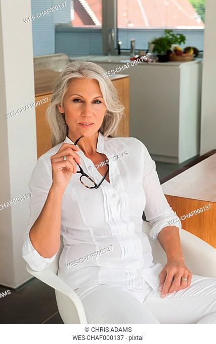 Portrait of mature woman sitting in her kitchen