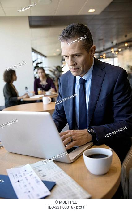 Businessman working at laptop and drinking coffee in airport lounge
