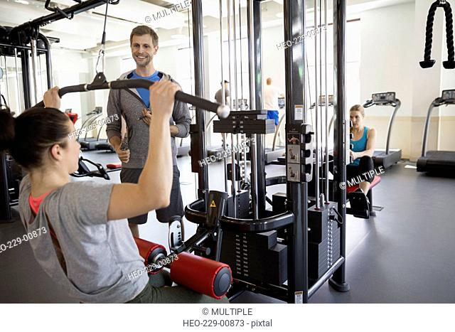Woman doing lat pulldown exercise at gym