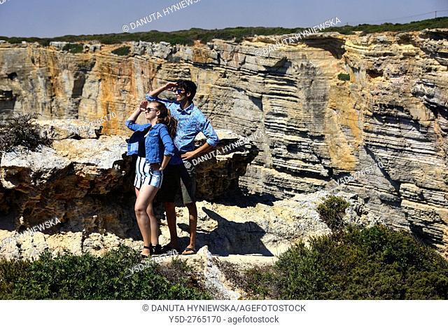 Young couple, in background monumental cliffs near Cape St. Vincent - Cabo de São Vicente, Costa Vicentina - Vicentine Coast, Sagres, Vila do Bispo, Algarve