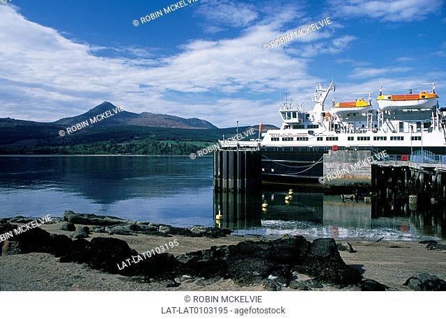 Inlet,bay. View to Goatfell mountain peak. Transport,Caledonian MacBrayne ferry at dock