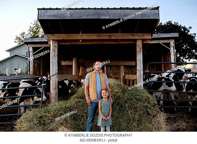 Portrait of father and daughter beside cow shed
