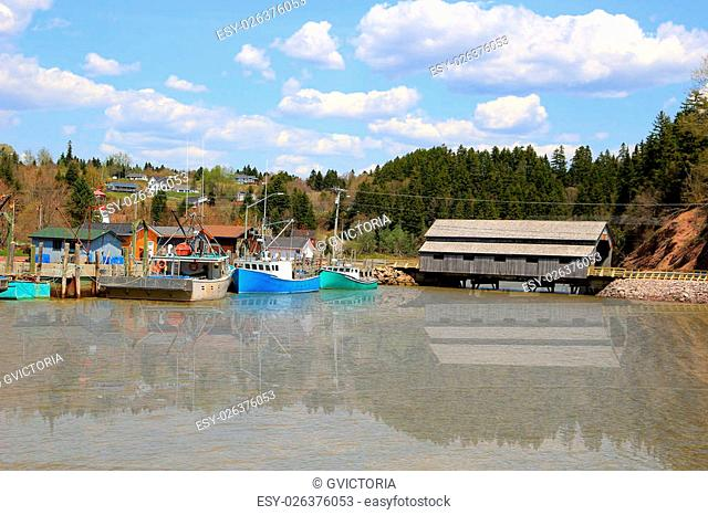 Boat and covered Bridge in St. Martins, New Brunswick during High Tide on the Bay of Fundy, Canada
