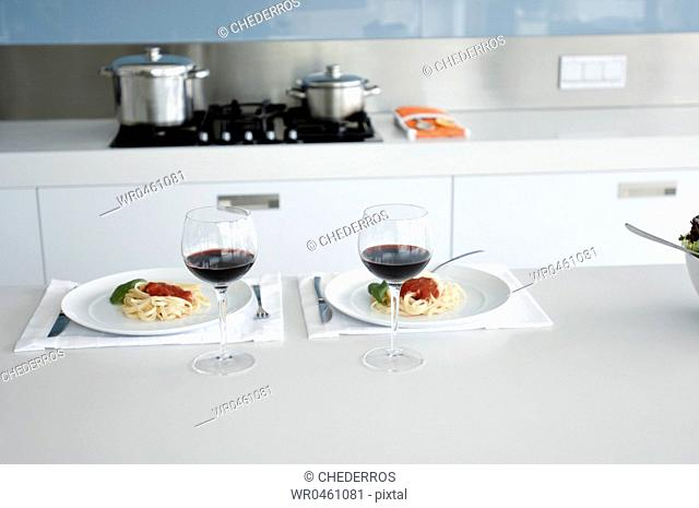 Two glasses of red wine and two plates of spaghetti on the kitchen counter