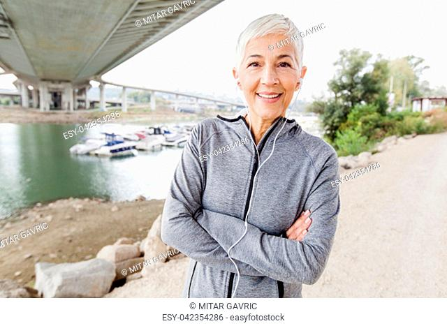 Smiling Senior Woman Relax Listening Music With Earphones After Running, Gray-Short Hair, Wear Sports clothes ,Workout Outdoor